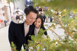 Young couple closely looking at Christmas tree together