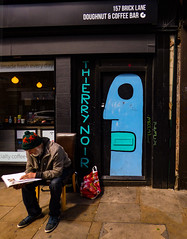 A Coffee Table Book (Steve Taylor (Photography)) Tags: 157 bricklane thierrynoir doughnut coffee bar bag woolyhat reading sitting cafe head face graffiti mural streetart tag chair black blue green red brown calm man book