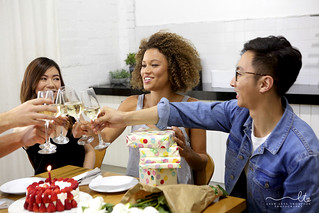 Diversity group celebrating birthday with cake and champagne
