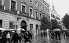 IMG_2083_1  Lluvia en la Puerta del Sol.   Madrid. (blanferblanc) Tags: madrid puerta delsol plaza lluvia paraguas arbol acera ciudad ventana balcón monocromo
