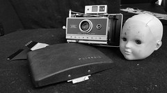 Eyes. (helioshamash) Tags: doll head polaroid land camera still life black white monochrome peelapart film dirty carpet