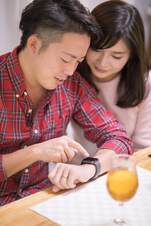 Young husband operating smart watch at home