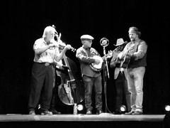 The Outliers Black And White. (dccradio) Tags: lumberton nc northcarolina robesoncounty inside indoors carolinaciviccenter historic historical historictheater theater theoutliers outliers bluegrass music concert livemusicband stage microphone fiddle violin uprightbass standupbass bass acoustic acousticguitar guitar mandolin banjo stringedinstruments musicalinstruments curtain blackbackground band people musicians blackandwhite bw blackwhite samsung galaxy smj727v j7v cellphone cellphonepicture