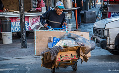 2017 - Mexico - Guadalajara -  Handtruck (Ted's photos - For Me & You) Tags: 2017 cropped guadalajara mexico nikon nikond750 nikonfx tedmcgrath tedsphotos tedsphotosmexico vignetting guadalajaramexico guadalajarajalisco ballcap streetscene street people peopleandpaths handtruck wheels amos cardboard poor needy male moustache curb sidewalk