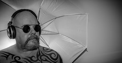 In the shade of the umbrella. . . (CWhatPhotos) Tags: cwhatphotos umbrella light lighting prop steampunk steam punk round sun shades glasses tattoo tattooed tattoos tatts tat tribal ink inked eyes moody mad torso upper body goatee photographs photograph pics pictures pic picture image images foto fotos photography that have which with contain mk digital camera lens micro four thirds em5 ii me man male self portrait selfee selfie mine face dark shadow studio lights shadows jbl headphones phones bluetooth e50bt