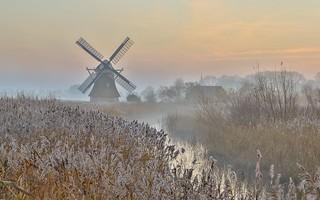 Wooden windmill in hazy landscape