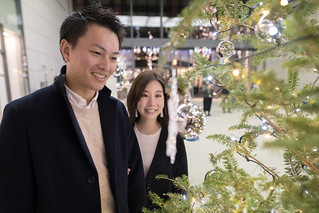 Young wife and husband looking at Christmas tree