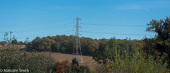Standing In The Field (M C Smith) Tags: pentax k3 field hedges trees green blue clouds white powerlines brown hill slope