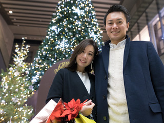 Happy wife and husband standing together in front of Christmas tree