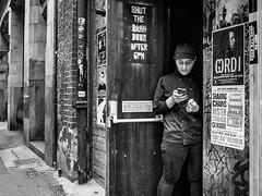 Northern Quarter 171 (Peter.Bartlett) Tags: manchester noiretblanc woman wall unitedkingdom urbanarte people urban city doorway peterbartlett streetphotography standing door smoking lunaphoto candid girl poster monochrome uk m43 microfourthirds olympuspenf bw niksilverefex sign blackandwhite cigarette cellphone england gb