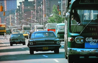 Lieutenant Kojak zooms along Central Park West in his NYPD-issued brown Buick Century chasing an evil suspect suspect in this shot. That bus with the Gilby's Gin sign presents no obstacle at all. 1973