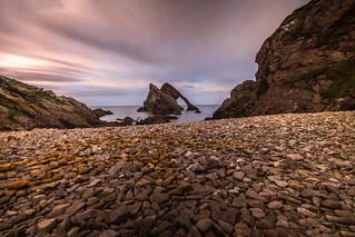 fine art colour long exposure view across the stony beach to Bow Fiddle Rock, Portknockie, Moray, Scotland
