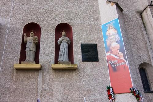 Figury na elewacji nowego kościoła w Haczowie i tablica pamięci ofiar Katastrofy Smoleńskiej