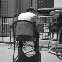 his-back-to-me (kaumpphoto) Tags: rolleiflex 120 tlr urban street man chair shadow pattern city minneapolis patio redbull profile bw monochrome windows building nike shoes laces logo smoking cigarette bar fence