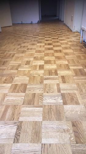 An oak mosaic parquet floor with a stain finished today ready for new skirting boards.