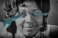 I'm Torn (Daz Smith) Tags: dazsmith fujixt20 fuji xt20 andwhite bath city streetphotography people candid portrait citylife thecity urban streets uk monochrome blancoynegro blackandwhite mono face ripped poster blue eyes black woman
