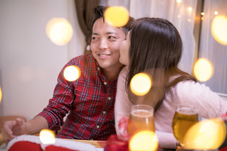 Young wife kissing to husband at Christmas night