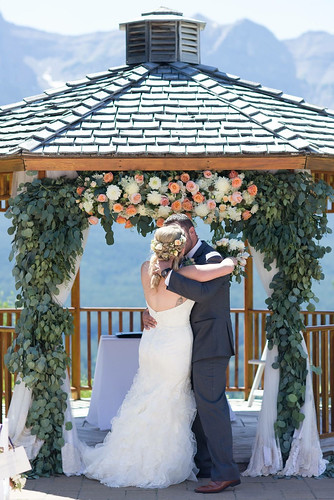 bride and groom kissing by silvertip gazebo, Flowers by Janie