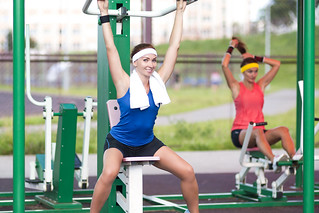 Sport Concepts.Two Positive Caucasian Female Athlete in Good Fit Having Training Outdoors. One is Staring Straight At Camera and Smiling