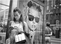 Shhh! (Steve Lundqvist) Tags: new york usa states united america manhattan stati uniti travel trip viaggio urban city urbanscape portrait ny nyc persone ritratto street road fujifilm x100s crossroad streetphotography times strada billboards ad advertising glass sunglasses glasses women stop bus victoria secret sidewalk juxtaposition rolex cell mobile