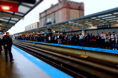 waiting it out (KevinIrvineChi) Tags: belmont ctaredline chicagotransitauthority illinois platform people peoplewatching commuters commuting purple brown urban cta curbedchicago boingboing sony dscrx100 lakeview detectable warning apartmentbuildings brick canopy rainy jackets coats overcast rain precipitation tiltshift aperture priority rail railroad railroadtracks vanishing point waiting