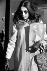 h102-69 23 (ndpa / s. lundeen, archivist) Tags: nick dewolf nickdewolf photographbynickdewolf blackwhite bw 1969 1960s 35mm film monochrome blackandwhite streetlife streetphotography charlesstreet beaconhill sidewalk candid people boston massachusetts ma city citylife sliceoflife spring march sunday weekend march9 youngpeople pedestrian winter door woman youngwoman brunette longhair coat glasses sunglasses shades bag paperbag carryingapaperbag purse handbag gloves furcollar shadows