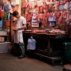 """butcher and his smartphone"" (hugo poon - one day in my life) Tags: x100f hongkong northpoint chunyeungstreet streetlife market vanishing citynight longnight butcher smartphone colours red meat crystalpoon browse phone"