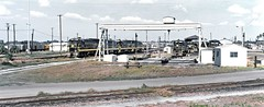 Seaboard Coast Line diesel electric locomotives are seen in the maintenance and shop area of the old railroad yard in Lakeland, Florida, 1974 (alcomike43) Tags: seaboardcoastline scl atlanticcoastline seaboardairline sal acl railroads trains freighttrains yard railroadyard shop maintenancefacility buildings crane ge generalelectric locomotives engines dieselelectriclocomotive u18b 345 alco c420 tracks rails rightofway freightcars hoppers boxcars photo photograph slide color old historic vintage classic lakelandflorida