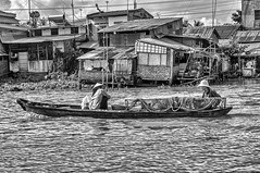Going Fishing (gecko47) Tags: fishing canoe net vinhlong vietnam bw blackandwhite river houses shacks waterfront buildingmaterials textures riverbank mekongriver cramped haphazard powerlines
