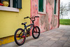 Burano Bike (~Arles) Tags: houses colorful grass plant outdoors burano venice italy shutters cloudy