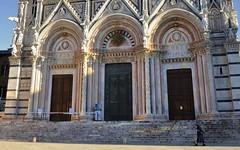 Duomo di Siena, Tuscan Romanesque lower façade, 1284-1370. (edk7) Tags: nikond60 nikonnikkor18200mm13556gedifafsvrdx edk7 2008 italy italia tuscany toscana siena architecture building oldstructure sculpture stonecarving city cityscape urban cattedralemetropolitanadisantamariaassunta cathedral duomodisiena romancatholic building12151263 facciata12841370 façade12841370 medieval frenchgothic tuscanromanesque classical church steps person nun habit female window door arch