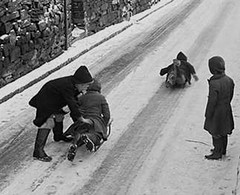 It is not impossible to slide up a hill (theirhistory) Tags: boy children kids snow ice road street coat wellies trousers wellingtons hat child kid pond water net rod village jacket buildings roads boots