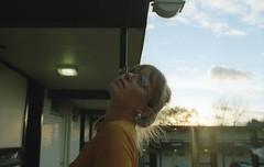 Charlotte Parker (fraser_west) Tags: film 35mm analog canon eos3 kodak gold sunlight sunset motel uk portrait girl youth colour light naturallight filmisnotdead wetheconspirators 2017 glasses retro cinematic sky sun december