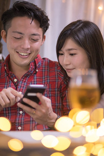 Young couple using smart phone at Christmas night
