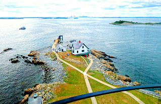 On top of Boston Light (Little Brewster Island) with the lighthouse keeper's house below, city skyline in the distance and a few harbor islands.
