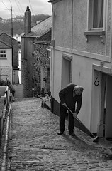 Sweeping at No6 (Mister Oy) Tags: davegreen oyphotos ©oyphotos streetphotography blackandwhite mono monochrome fujix100f cornwall stives sweeping cobbles old man hill slope