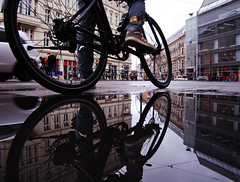 rain is not a barrier to take a bike (Ismail - humanistic misanthrope ツ) Tags: rain berlin hackescher markt pfütze puddle bike fahrrad spiegelung there is no bad weather clothes autumn reflection perspective adidas