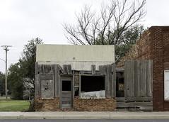 Keyes, Oklahoma (unknown quantity) Tags: unpaintedwood openwindows corrugatedmetal masonry crumbling utilitypole wires abandonedbusiness weathered deterioration fadedpaint rot barewood trees cloudy