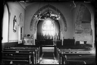 Church interior showing altar and pews. Script over altar reads