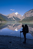 Kinney Lake Silhouette (robertdownie) Tags: sky water reflection clouds rock snow ice mirror bluesky still cliffs symmetry tranquil wilderness tranquility remote backcountry forest canada lake mountains bc britishcolumbia kinneylake mtrobsonprovincialpark oneperson silhouette hiker hiking trekking walking walkingpoles bushwalking backpacking