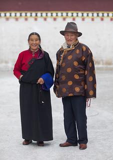 Portrait of a tibetan couple in traditional clothing in Rongwo monastery, Tongren County, Longwu, China