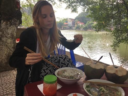 Julie déguste son Phở en buvant de l'eau de coco !