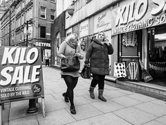 Northern Quarter 175 (Peter.Bartlett) Tags: manchester bag noiretblanc women shopfront unitedkingdom people facade doorway woman walking urbanarte cigarette streetphotography lunaphoto peterbartlett urban monochrome candid uk m43 couple olympuspenf bw niksilverefex sign blackandwhite microfourthirds city england gb