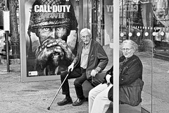 bus stop (susanjanegolding) Tags: advertisement bench publictransportation oldwoman oldman latelove oldage newyorkcity busstop callofduty monochrome blackandwhite fujifilm xpro2