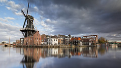 Haarlems icoon (zsnajorrah) Tags: urban city landscape photography windmill mill bridge water river reflection boat transportation sky overcast clouds darkclouds gatheringstorm longexposure neutraldensityfilter nd filter breakthrough breakthroughphotography x4nd10 tiffen gradnd sirui tripod canon dslr 7dmarkii efs1018mm netherlands nederland noordholland haarlem spaarne adriaan zuidam scheepmakersdijk catharijnebrug koudenhorn explore