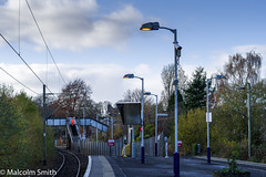 The Branch Line Station (M C Smith) Tags: pentax kp platform cctv signs lamps steps bridge footbridge station plants trees hedges green blue clouds white fence mirror gritbin yellow ticket machine lights hivi orange man track ballast overheadcables numbers letters symbols houses