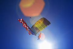 Visions of Icarus (CameraOne) Tags: flying sun airborne altitude falling sailing gliding parachutes wings icarus flight skyward backlight usa flag starsandstripes decent floating canon6d canonef28135 zoom raw cameraone blue