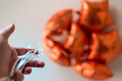 Orange (Chancy Rendezvous) Tags: orange balloons balloon string mylar foil hand ceiling bokeh blur dof depthoffield fingertips