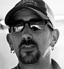 Swamp Monster. (Neil. Moralee) Tags: neilmoralee usa2017neilmoralee man face portrait candid working cap hat swamp monster earing moustache beard glasses reflection bright subshine cajun encounter tour guide creature close black white bw bandw blackandwhite mono monochrome neil moralee nikon d7200 new orleans louisiana natgeofacesoftheworld