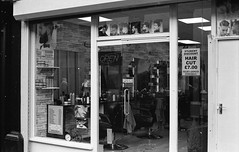 Preston Barber Bergger Pancrp 400 (Man with Red Eyes) Tags: barber shopwindow preston lancashire northwest nikonf6 50mmf18ai analog analogue blackwhite monochrome silverhalide berggerpancro400 d76h divided modified anchelltroop 5minsa5minsb v850